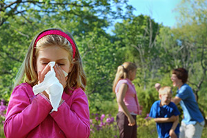 Young girl blowing her nose into a tissue - Omaha NE